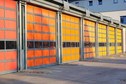 Rote, gelbe und orange Garagentore eines Feuerwehrhauses