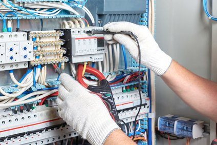 The senior electrician with a diagnostic tool in his hand, standing next to the electrical panel, measures the performance of electrical circuits.