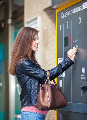 Frau bezahlt am Kassenautomat eines Parkhauses